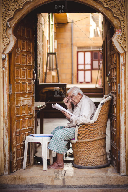 Jaisalmer, India - November 9, 2014: Elderly man reading a newspaper in Jaisalmer, Rajasthan, India