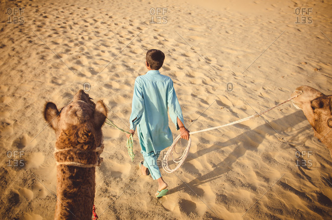 Boy walking with a camel in the Thar Desert, Rajasthan, India