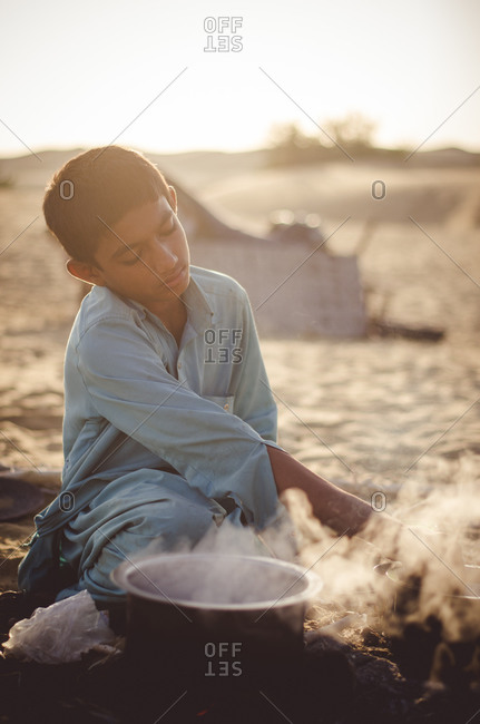 Thar Desert, India - November 10, 2014: Boy preparing food in the Thar Desert in Rajasthan, India
