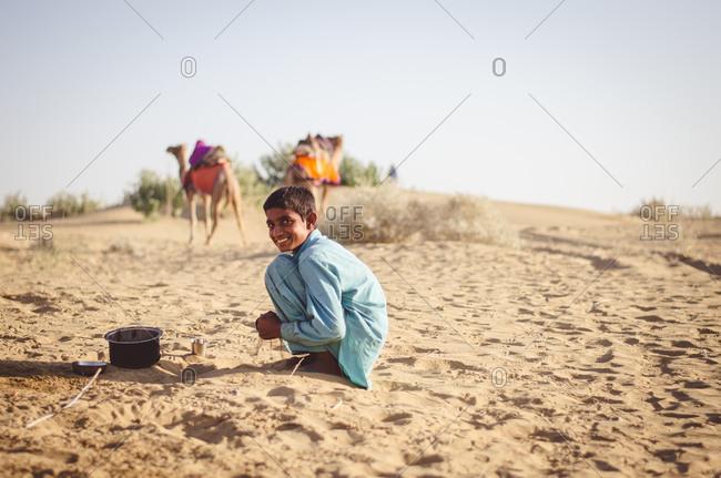 Thar Desert, India - November 10, 2014: Boy cooking in the Thar Desert in Rajasthan, India