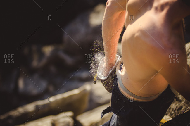 Man getting more chalk on his hand as he climbs