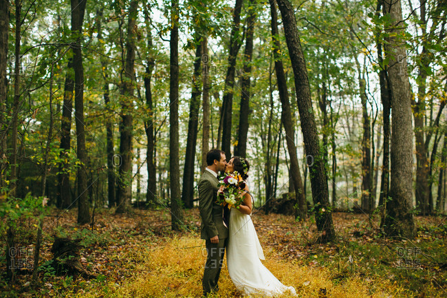 Bride and groom kissing in a forest