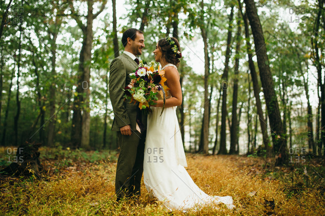 Newlyweds standing in a forest