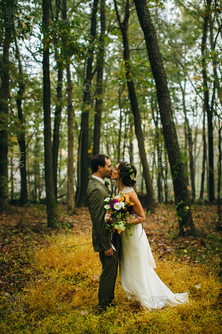 Newlyweds kissing in a forest