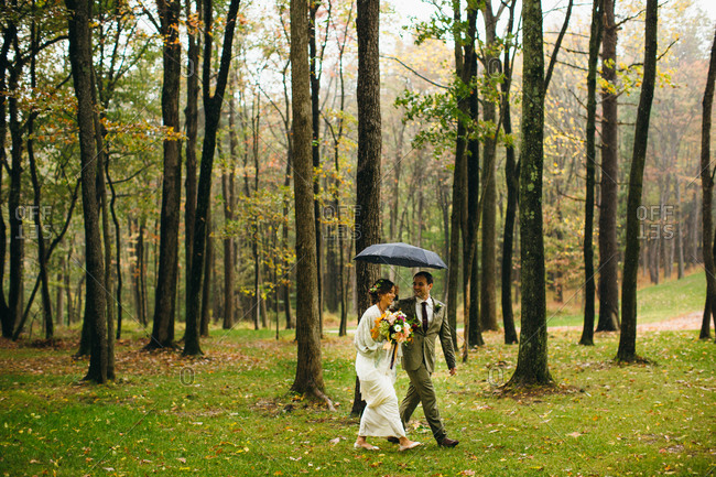 Groom holding an umbrella for his bride