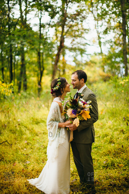 Bride and groom standing in the woods