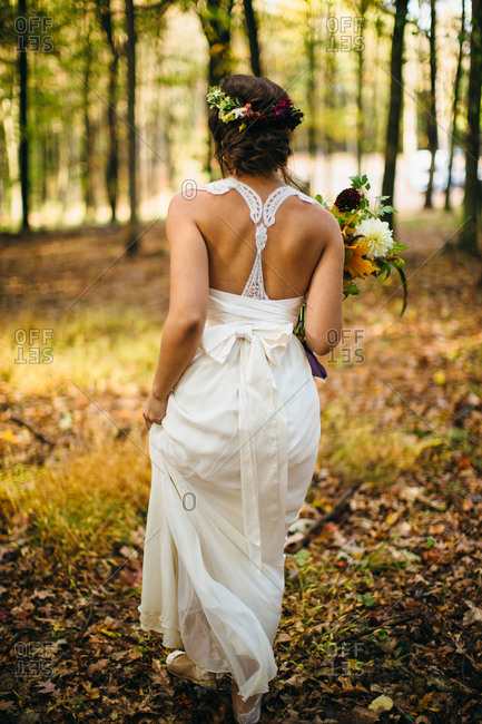 Back view of bride walking in a forest