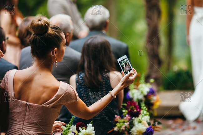 Woman snapping a picture with her smartphone at a wedding ceremony