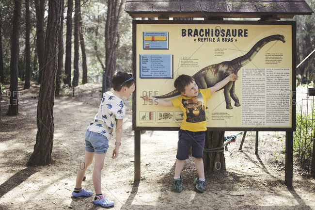 Meze, France - April 3, 2015: Two boys reading sign at the Musee Parc Des Dinosaures