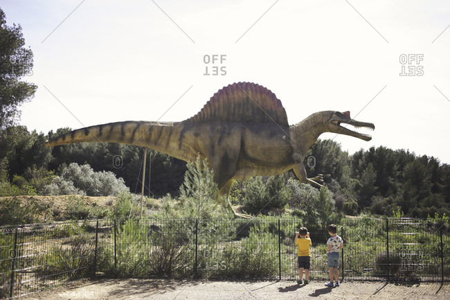 Meze, France - April 3, 2015: Young boys looking at dinosaur statue in the Musee Parc Des Dinosaures
