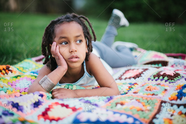Young girl daydreaming on a blanket