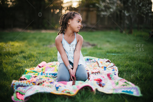 Young girl kneeling on a blanket outdoors
