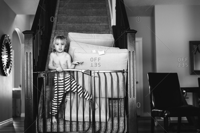 Child stacking cushions behind a safety gate