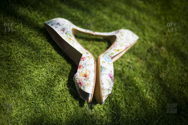 A bride's pair of wedding shoes on green lawn