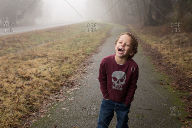 Portrait of little boy on a foggy road