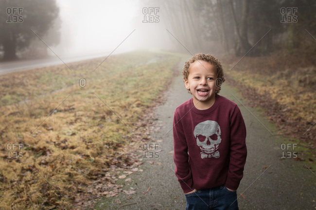 Portrait of boy standing on a foggy road