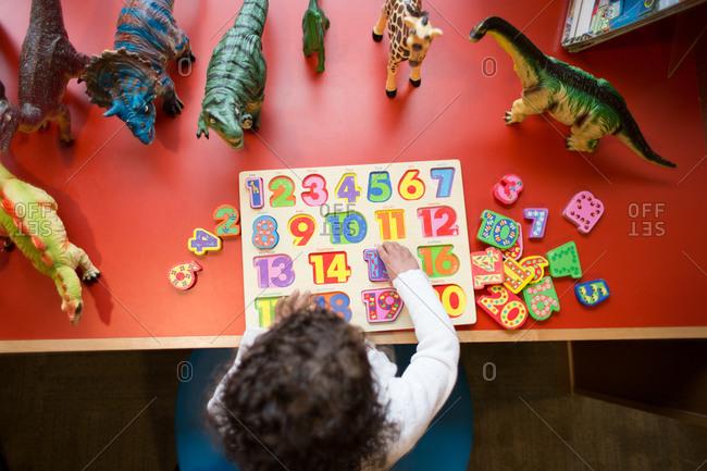 Little girl assembling an educational puzzle