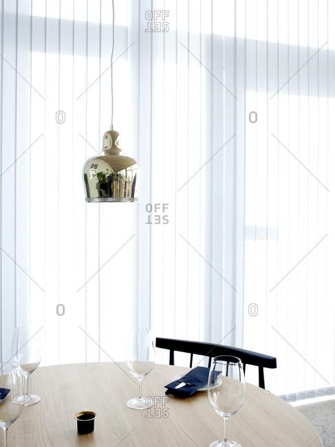 A restaurant table underneath a metal pendant light