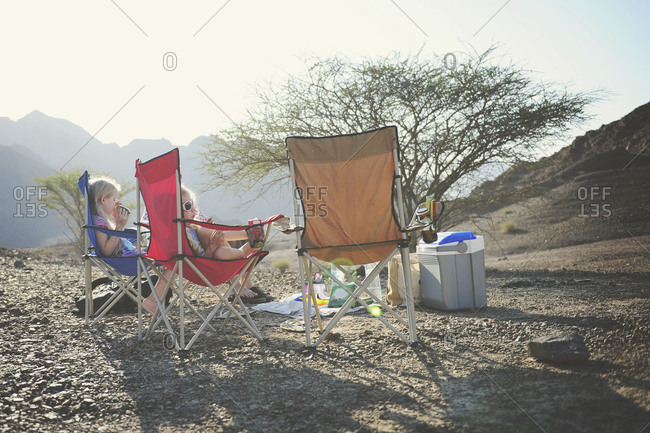Young girls relaxing in camping chairs