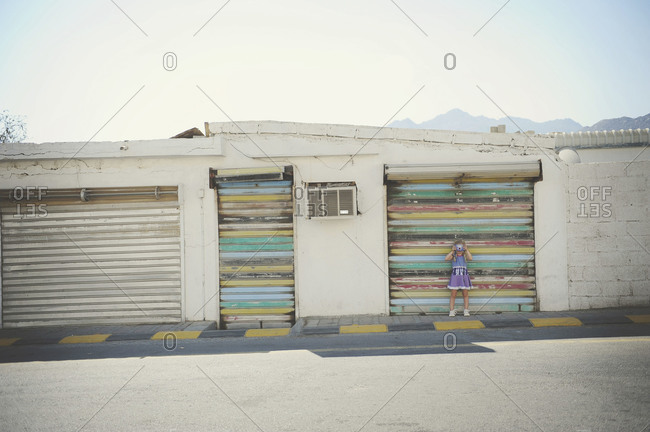 Young girl taking pictures on an empty street