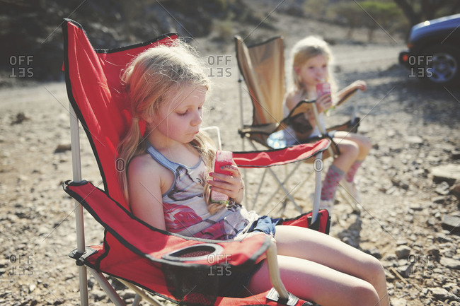 Twin sisters drinking in camping chairs