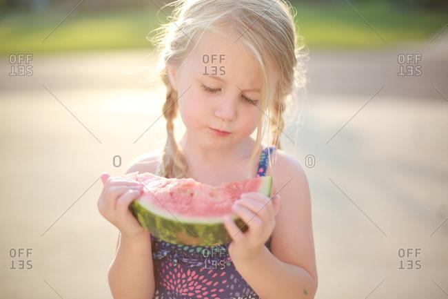 A little girl in a babysitter eats a watermelon
