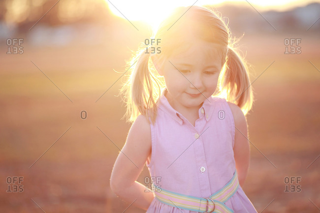 A little girl in ponytails in the sunlight