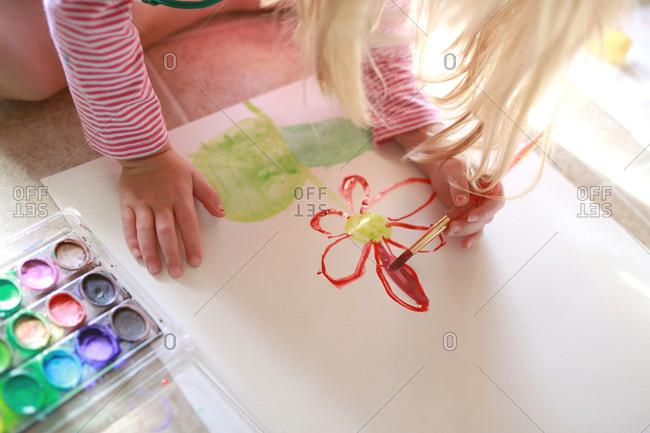 A little girl paints a flower