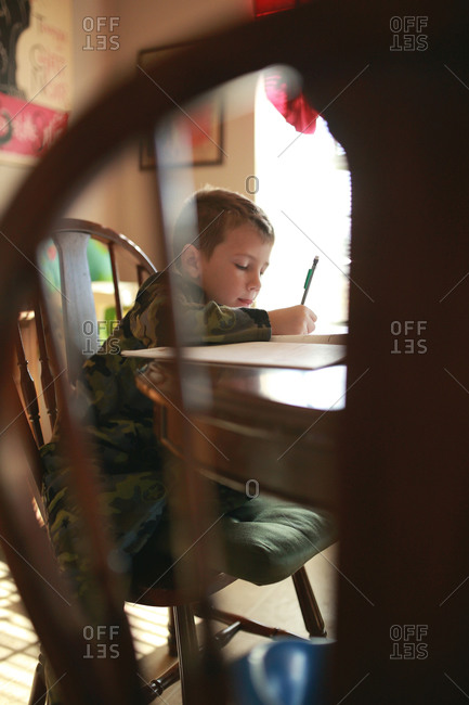 A little boy in army pajamas does homework