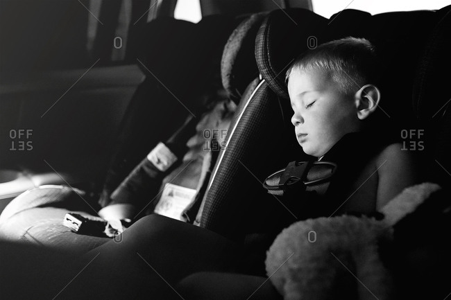 A little boy naps in his car seat