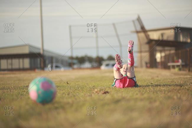 Little girl falling on her back in a soccer field