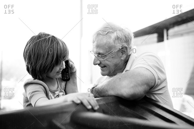 Young girl using a phone next to her grandfather