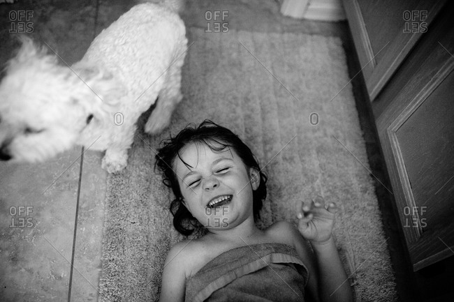 Young girl laughing next to a dog