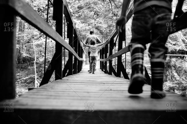 Children walking on a wooden bridge