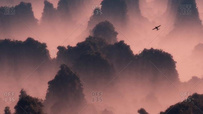A small airplane flies through misty mountaintops in pink evening light