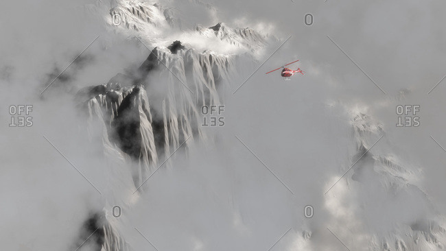 A red helicopter flying above jagged snow-covered mountain peaks