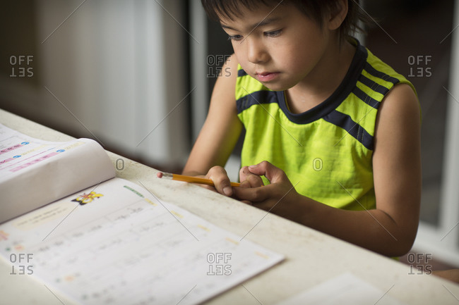 A Japanese boy doing his Japanese homework in a kitchen