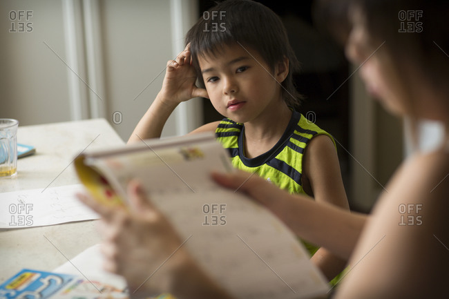 A Japanese boy studies Japanese homework in a kitchen as his mom helps him