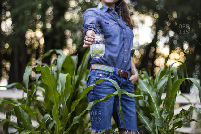 Woman stands in her garden drinking a gin and tonic during the summer