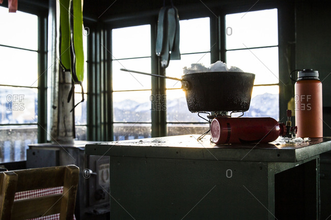 Melting snow on a camp stove in an old fire lookout in Montana