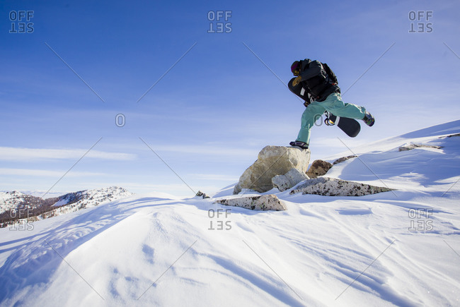A snowboarder jumps to a rock at the top of a mountain while carrying his snowboard