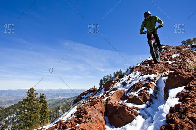 A man rides his fat tire bike along a partially snow covered rocky section of the Crest Trail in Big Cotton Wood Canyon, Utah