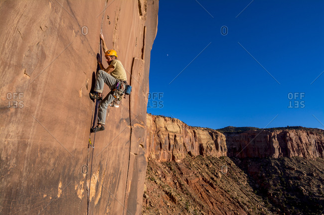 A man rock climbing up a difficult crack called Sig Sauer at the Pistol Whipped Wall in Indian Creek, Monticello, Utah