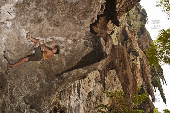 Woman bouldering on limestone cliffs at Railay beach in Thailand