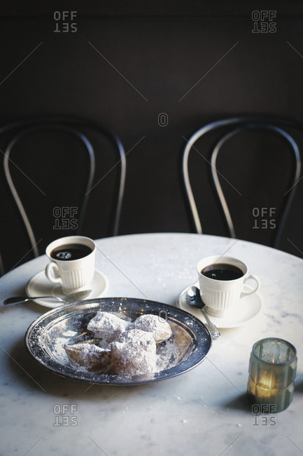 Two cups of coffee and a tray of sugared pastries