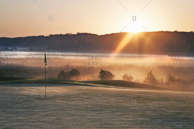 Glowing dawn light on a golf course green The sun just appearing above a mountain range