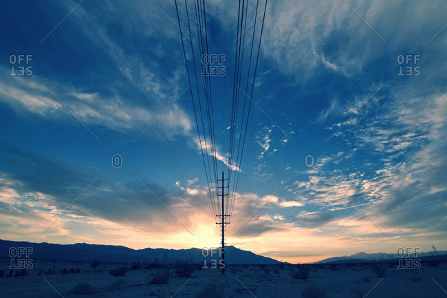 Power lines on poles reaching into the distance, in a mountain landscape
