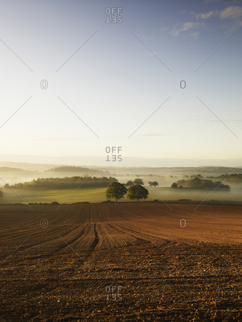 A ploughed field and view over surrounding undulating hills, at dawn with a mist rising from the land