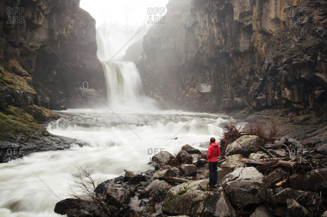 Woman watches water come tumbling down a rocky canyon