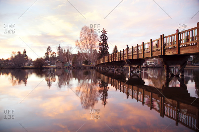 Man standing on a pedestrian bridge over water to watch the sunset
